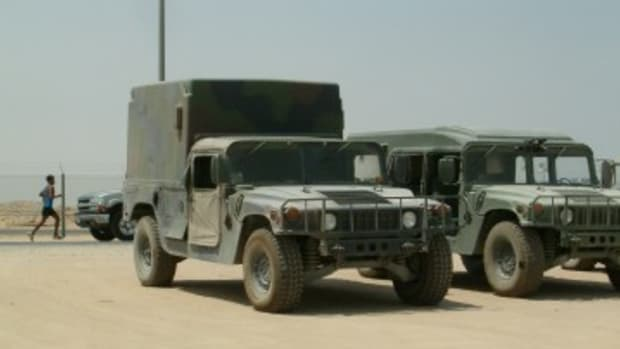 Taken in Kuwait in 2004, this photo shows two HMMWVs. The one on the left is painted in 3-color CARC.