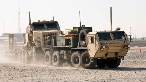 A Heavy Expanded Mobility Tactical Truck Wrecker tows a Heavy Equipment Transporter and trailer during a training exercise at Camp Arifjan, Kuwait. The trucks and the Soldiers who drive them make frequent trips into Iraq, retrieving equipment such as humvees, tanks and Mine Resistant Ambush Protected vehicles.