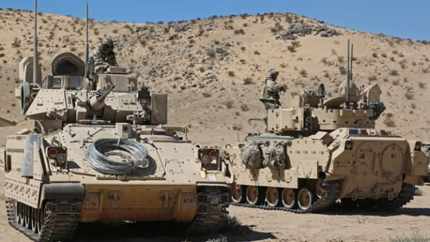 U.S. Army Soldiers from Alpha Company, 1st Battalion 77th Armored Regiment, maneuver their Bradleys into position during Decisive Action Rotation 14-10 at the National Training Center in Fort Irwin, Calif., Sept. 23, 2014. The decisive action training environment rotations were developed to create a common training scenario for use throughout the Army. (U.S. Army photo by Sgt. Charles Probst)