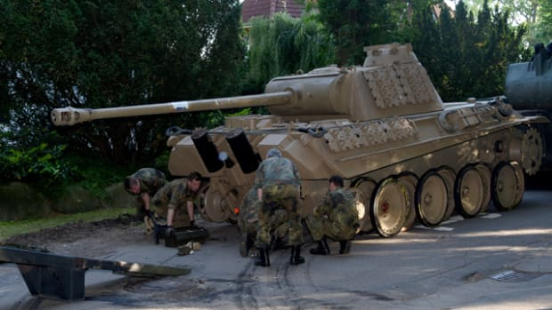 In this July 2, 2015, picture a World War II -era Panther tank is prepared for transportation from a residential property in Heikendorf, northern Germany. Authorities have seized a 45-ton Panther tank, a flak canon and multiple other World War II-era military weapons in a raid on a 78-year-old collector's storage facility in northern Germany.