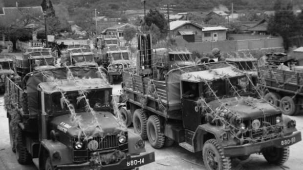 Troopers wait as 2 1/2 ton cargo trucks are loaded somewhere in Korea, June 1970. The vehicles are a mixture of horizontally and vertically exhausted naturally aspirated Multifuel trucks. In the foreground, a M35A2 that was scarcely a year old when this photo was taken. How do we know? – read on! National Archives and Records Administration photo
