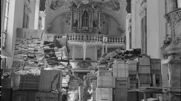 The Monuments Men encountered repositories such as this one all across Europe. Here, piles of boxes, records, and clothing are guarded by an American GI inside a church in Ellingen, Germany