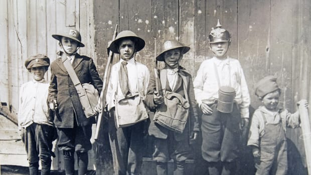 Group of kids playing army were photographed in 1920. The boy, second from the left is wearing a M1917 helmet decorated with the painted insignia of the 102nd Infantry Regiment. The boy fourth from the left is wearing a helmet that has a 101st Regiment insignia.