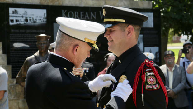 Retired Marine Staff Sgt. Eric Smith is awarded the Navy Cross by Maj. Gen. Paul J. Kennedy during a ceremony in Irving, Texas, Sept. 14. Smith was awarded the Navy Cross for courageous actions in 2004 while serving as a squad leader with Company E, Second Battalion, Fourth Marine Regiment, First Marine Division, in support of Operation Iraqi Freedom. Smith currently serves as a lieutenant paramedic with the Irving Fire Department. Kennedy is the commanding general of Marine Corps Recruiting Command and commanded 2nd Battalion, Fourth Marines at the time of Smith's actions. The Navy Cross is the second highest military decoration that may be awarded to a member of the United States Navy.