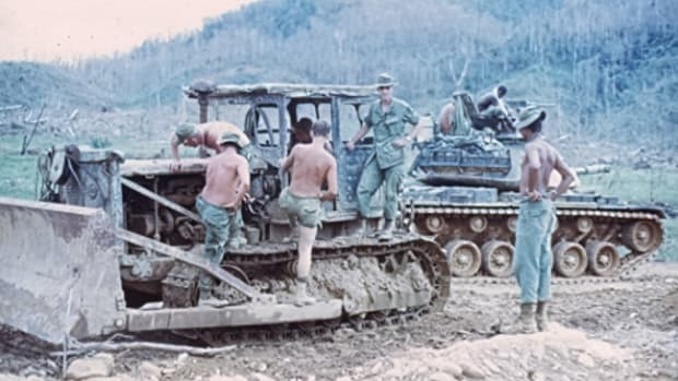 Combat Engineers inspecting recently captured Soviet copy of American dozer in the A Shau Valley. Note M48 tank and the defoliated trees in the background. Photo courtesy Engineer Magazine, July-Sept 2007. Engineer Museum, Ft Leonard Wood. Used with permission.