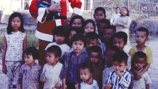 An American soldier dressed as Santa handing out candy to Vietnamese children.