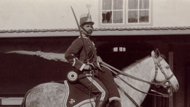 A 1907 dated image of  a Light Cavalryman. This time from a regiment that wore a silver trimmed sky blue shako. The headgear of the Cazadores de Caballería ran the spectrum from shako to fur busby to metal spiked helmet depending on the regiment. The uniform is sky blue trimmed white. The double breasted tunic would be replaced in 1909 with a single breasted model. His mount is decked out in  regulation horse furniture, also sky blue with white trim and the Cavalry branch insignia. He is armed with a Model 1895 Cavalry saber.