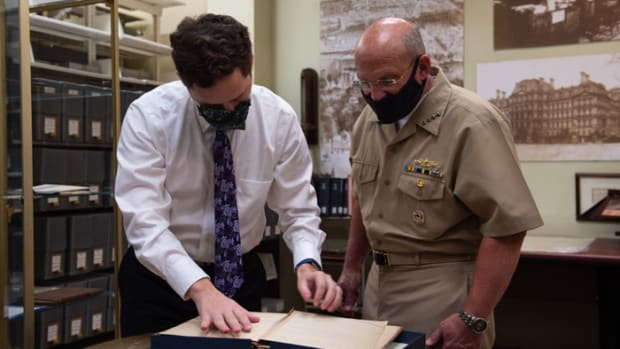 Mike Gilday and Dylan Beazer, a Department of the Navy Library librarian, view a historical navy document in the Navy Department Library's rare book room. Gilday toured the Navy Department Library after the ground breaking of the Operational Archives and Repository Complex. NHHC, located at the Washington Navy Yard, is responsible for the preservation, analysis, and dissemination of U.S. naval history and heritage.