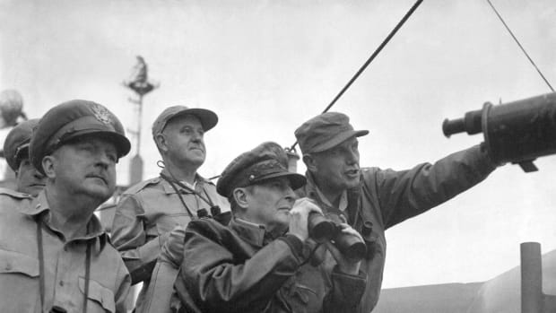 Brigadier General Courtney Whitney, government section, Far East Command; General Douglas MacArthur, Commander-in-Chief, United Nations Command, and Major General Edward Almond (at right, pointing), Commanding General, X Corps in Korea, observe the shelling of Incheon from the USS Mount McKinley (AGC-7), 15 September 1950.