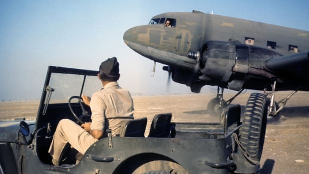 ALGIERS,ALGERIA - AUGUST 1943: A view as an US Air Force pilot looks out his window during take off, flying from Algiers to Tunis, Tunisia. Jeep sports lusterless blue registration numbers.