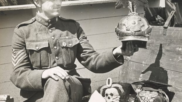 Sgt. G.M. Slade, Canadian Expeditionary Force, holding a German helmet of the Kaiser's Imperial Guard.
