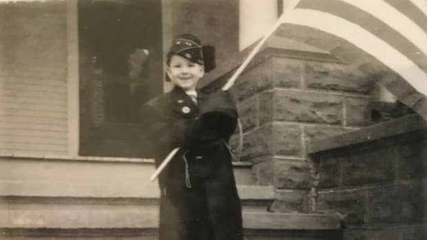 4-year-old John Adams-Graf wearing Milton Graf's American Legion cap and jacket holding a flag.