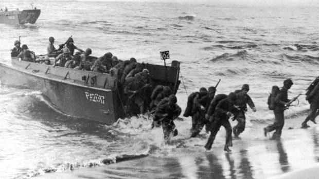 "A LCVP ""Higgins boat"" unloads a troops."