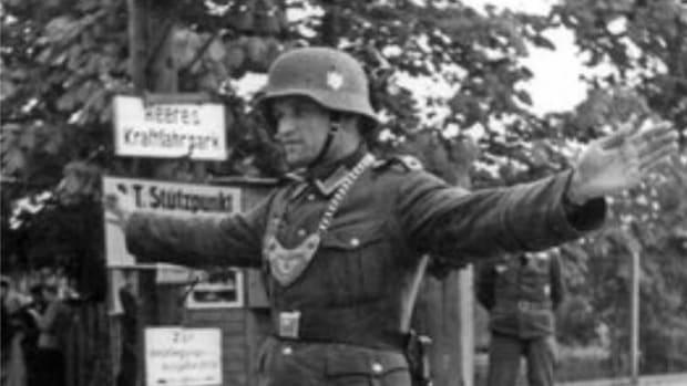 A German Feldgendarmerie/Wehrmacht Uniformed Police Officer directs traffic.