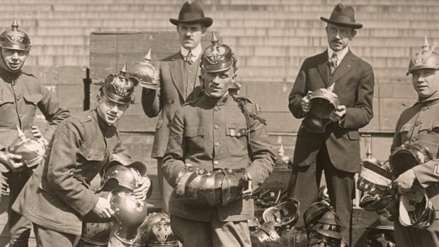 US soldiers and Treasury Dept. workers unpack captured German helmets to use in Victory Loan drives.