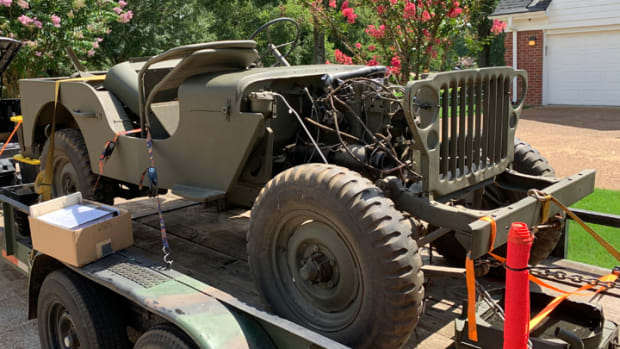 1943 Jeep on a trailer. No fenders, hood.
