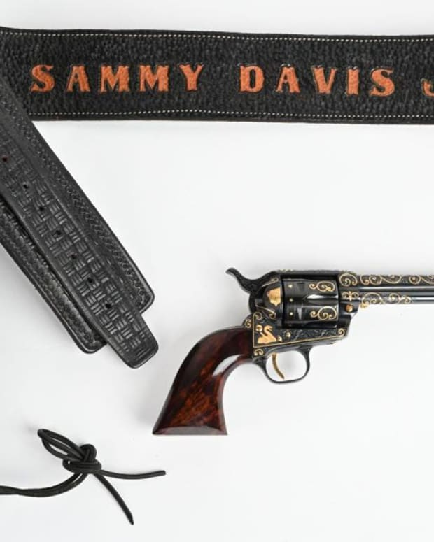 Sammy Davis Jr's .357 Magnum, 1965, with holster and belt bearing the entertainer's name. Master engraver Joseph Condon of Las Vegas expertly engraved and added gold inlays of Buffalo Head nickel, coyote, mountain lion, rattlesnake and more. Sold within estimate for $16,800.