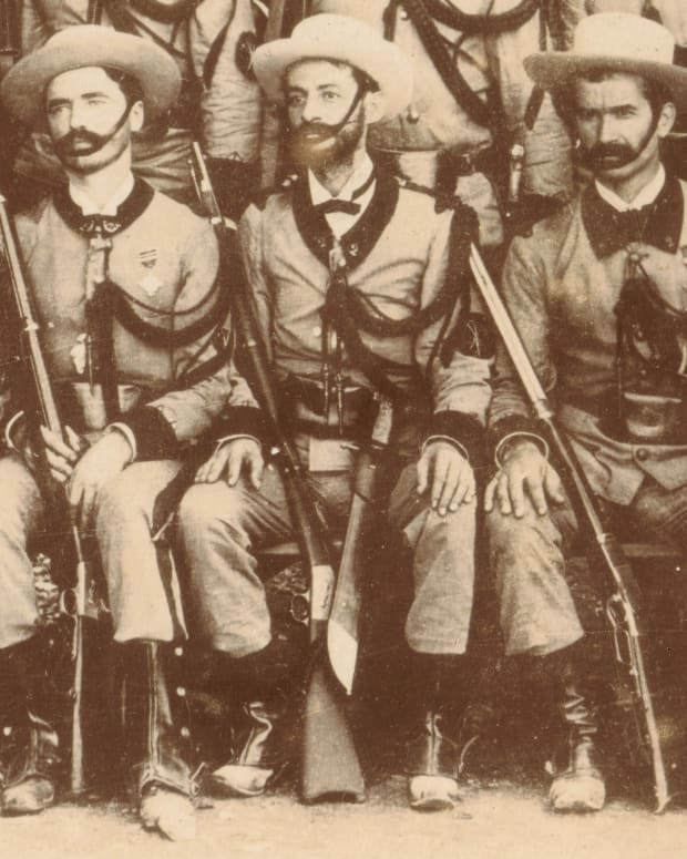 A detail view of a group photograph of the Gastadores section of the 2nd Havana Volunteer Infantry Regiment taken about 1895. The Modelo 1843 Infantry machete of the soldier in the center is clearly visible. Note also the crossed tools sleeve insignia and the thick aiguillette, all symbols identifying these elite Spanish Pioneer Infantrymen.