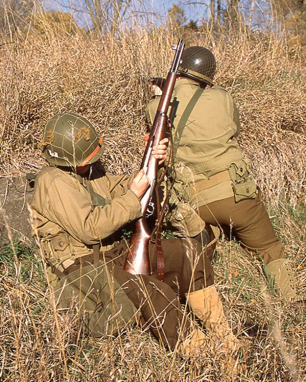 Two WWII US reenactors firing / loading M1 Garands