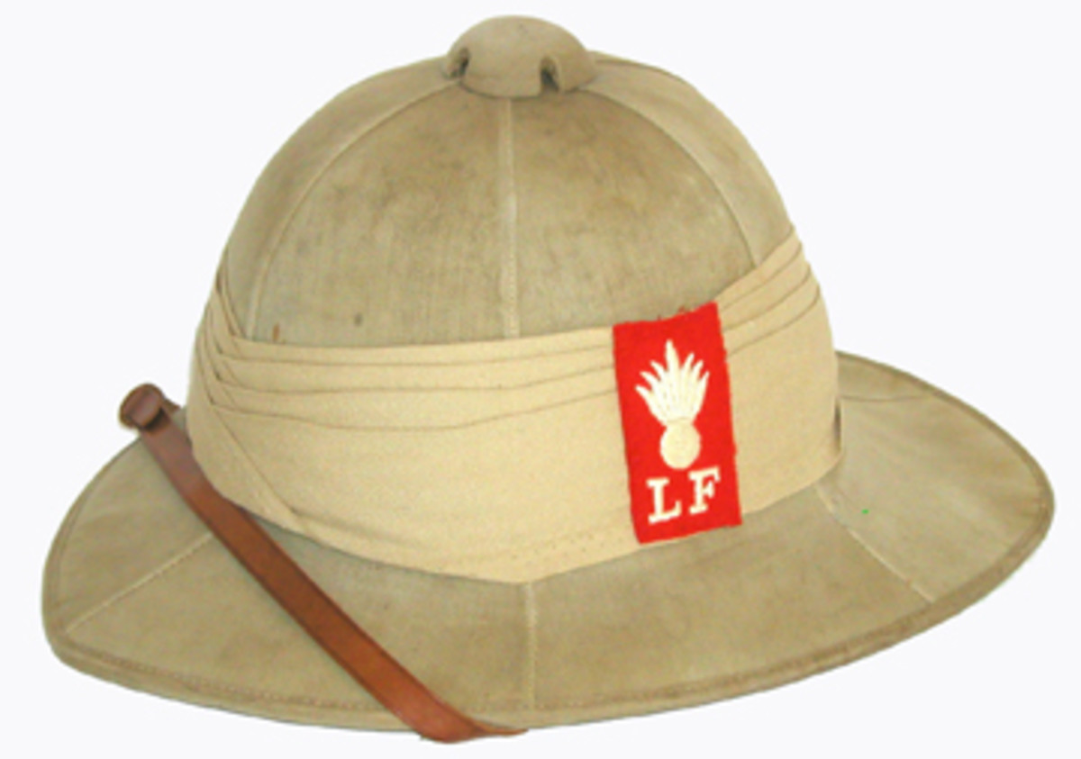 "Commonly called the ""topi,"" the Wolseley sun helmet was used during WWI and remained in service through WWII. The body is cork covered with khaki drill cloth that has six seams. This example is from the WWI period and features the patch of the Lancashire Fusiliers. This unit fought at the infamous Gallipoli campaign in 1915"