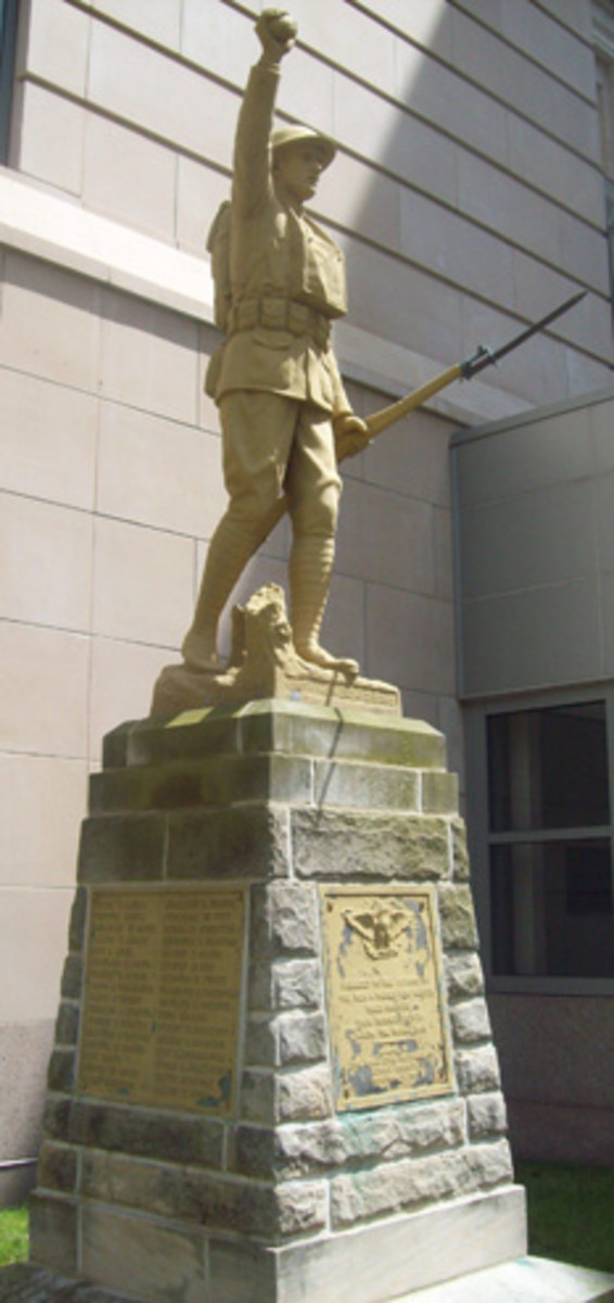 The full-size statue in Akron, Ohio, holds a grenade and a rifle with repaired bayonet. It appears to have been entirely coated with light tan paint.