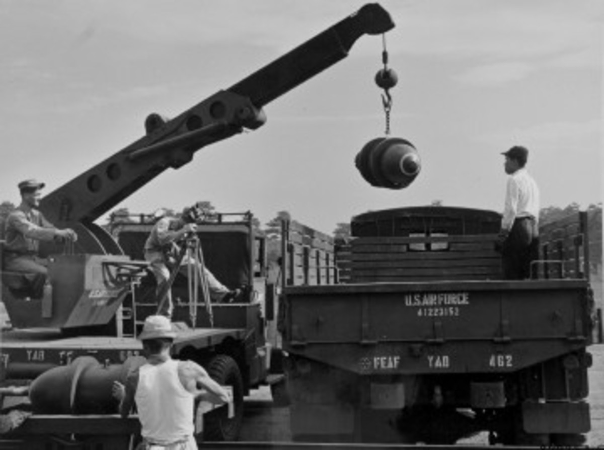 As a cameraman films the action, a 35th Supply Squadron U.S. Air Force M108 unloads bombs from a M211 GMC 2-1/2-ton truck. This scene unfolded somewhere in Japan in September 1955.