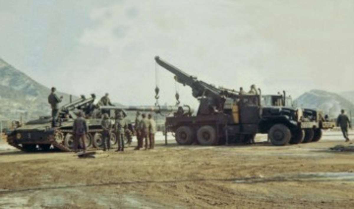 A pair of M543A2 wreckers work in tandem to change the 107mm barrel of a M175 self propelled gun at Camp St. Barbara in Korea.