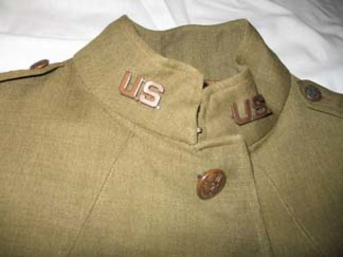 "Two high-quality bronzed ""U.S."" pinback insignia were affixed to the tunic's collars and match the ""U.S."" insignia on Father LeMay's overseas cap.The collars show evidence of pinback Chaplain's insignia that were removed at some point in the tunic's history."