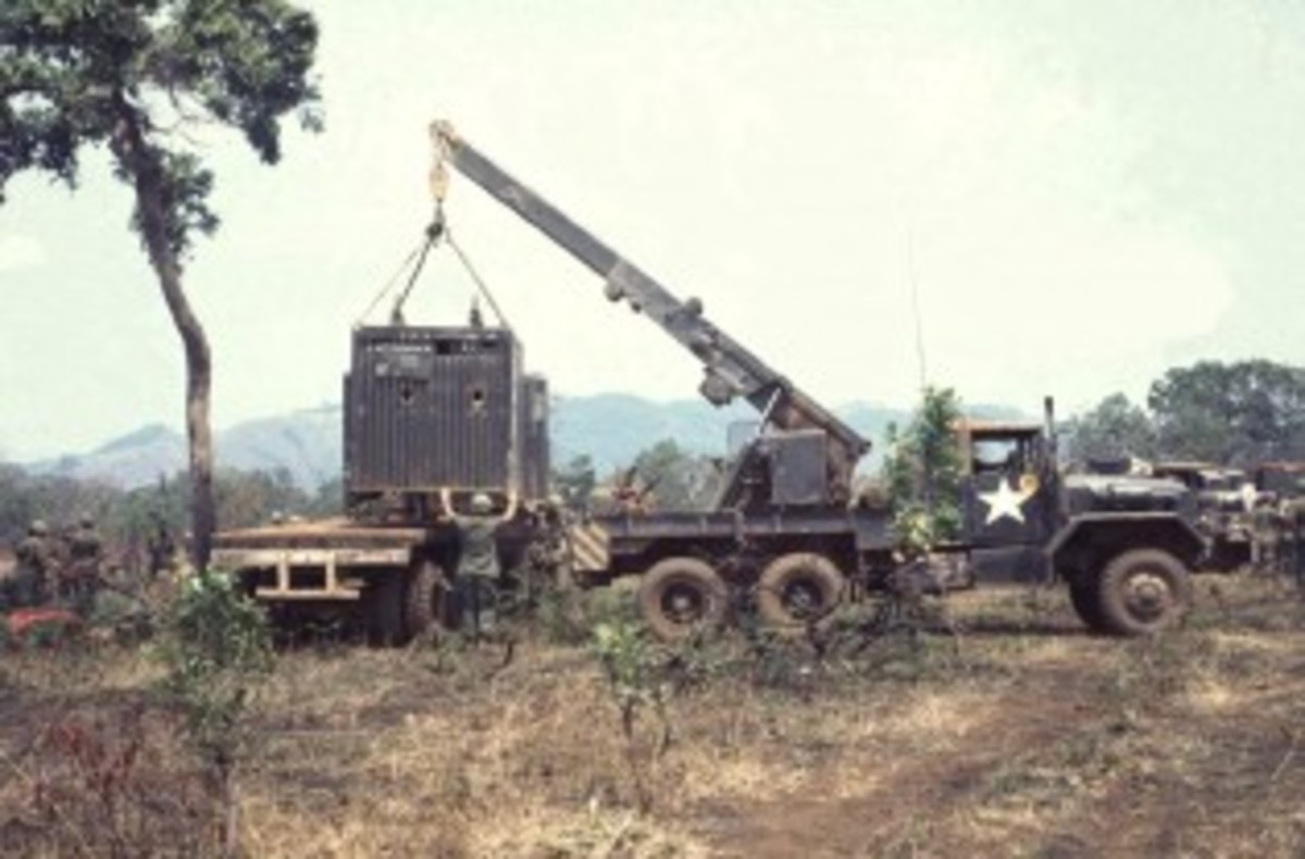 Somewhere in Vietnam, a M543A2 is used to load a Conex box onto a semi trailer. The boom is near full extension, and is not supported to the ground or the wrecker bed, by boom jacks.