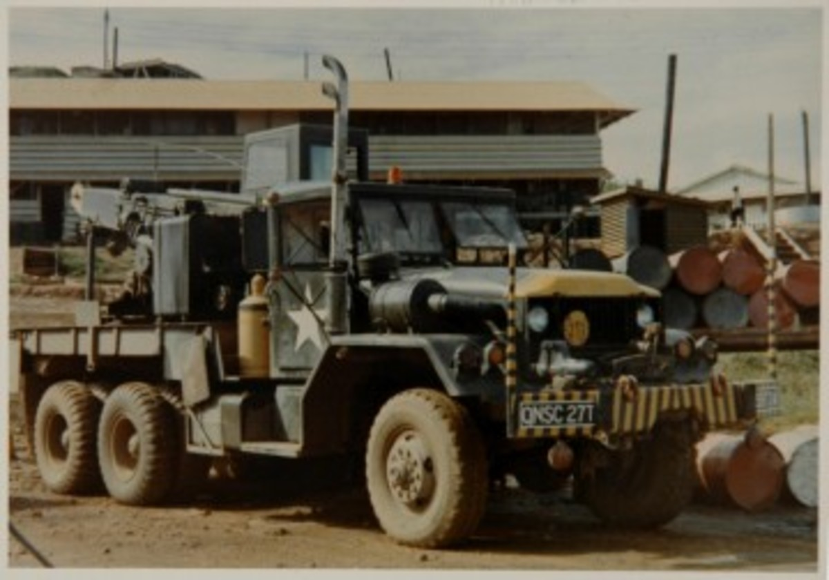 """Because wreckers were normally assigned to maintenance units that had tools, materials and skill, the trucks were subject to more """"customization"""" than most other vehicles. This M543A2 has been modified with the addition of a second hazard flasher, mounted on the right fender, an extended exhaust stack, and on the front bumper are guide poles and additional lights. Also note the additional lights on the rear view mirrors, the hard top enclosures for both the driver and crane operator compartments, and the lashed-down radio antenna."""
