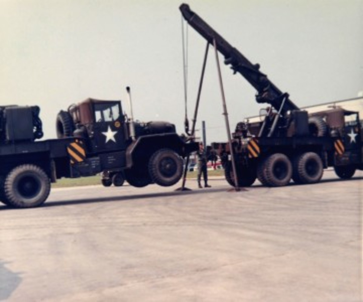 The M62 and later wreckers, including these M543A2 trucks, were equipped with stiff legs. Demonstrated here during a training exercise, these were used during heavy lifting operations to transfer the weight of the suspended load directly to the ground, preventing the boom from bending.