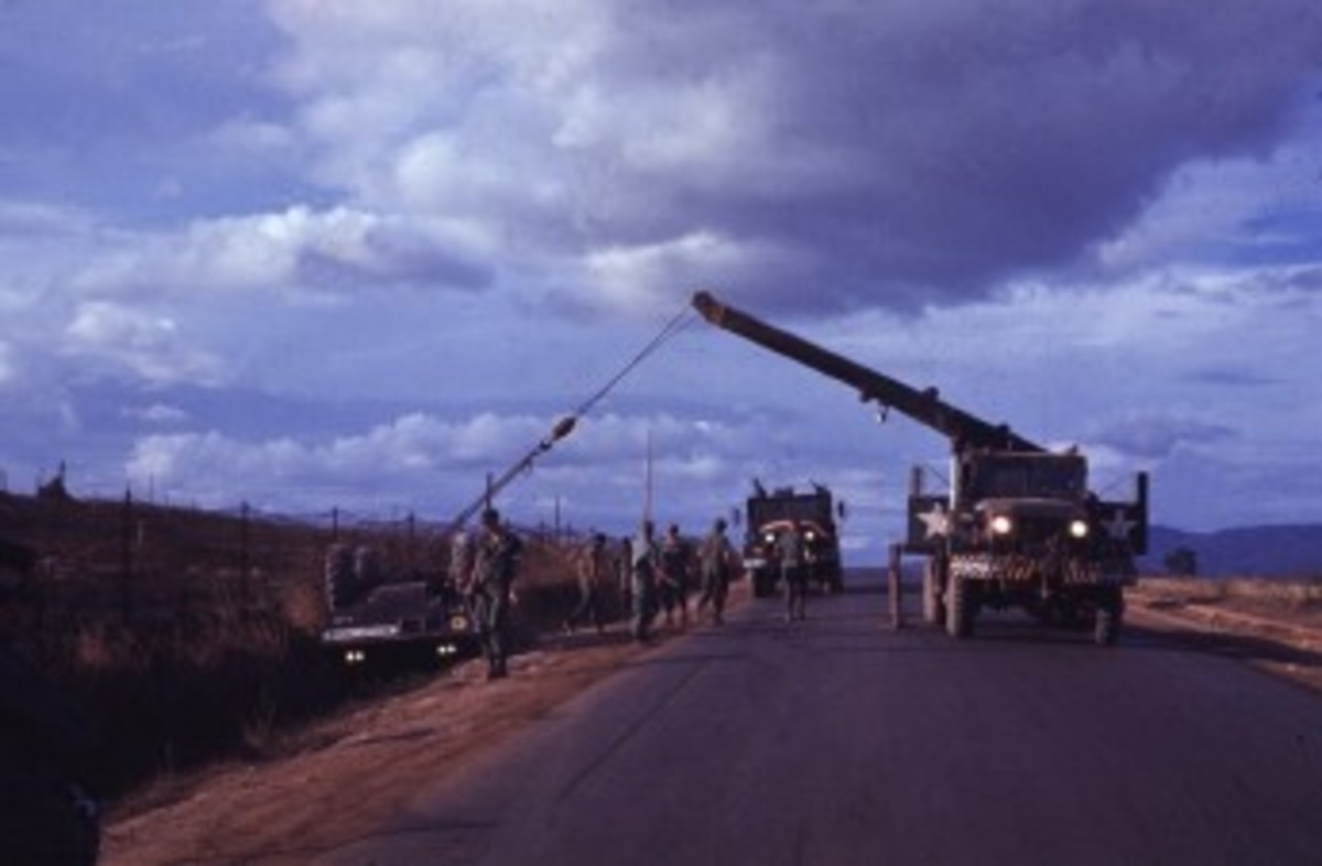 Somewhere in Vietnam the crew of a M543A2 wrecker prepares to right an overturned Cadillac-Gage Commando. A gun truck and its crew stand by in the event of an ambush. This is an excellent example of the forgotten conditions these crews--and their vehicles--worked under.