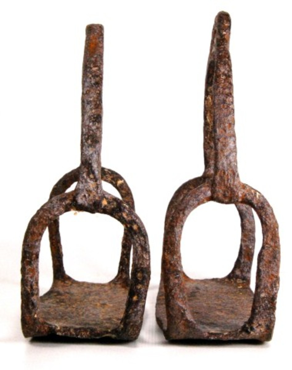 Lot# 579. Revolutionary War Iron Stirrups cut away sides and hand welded top strap with additional cutout. Nice overall undisturbed patina. 18th century. Estimate: $50-$100.