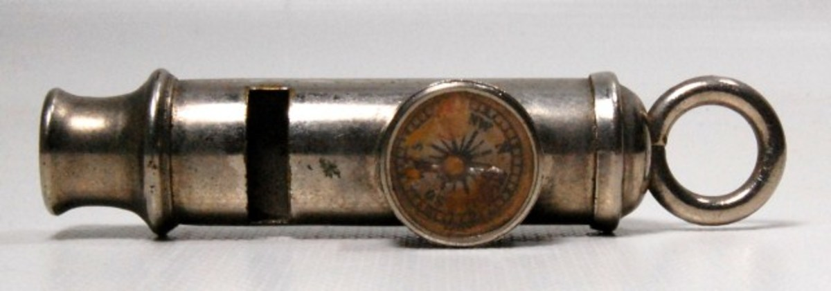 """Lot# 534. WWII Alfred De Courcy & Co, Escape Whistle with Compass. De Courcy model #187. Made to design 700919, 1923. Nickel plated brass. Most compass whistles are of the a dry magnetic type. Though this one seems to be inspired by liquid compasses as used in marine vessels. It is the classical design of what is known as the """"Escape Compass"""", often with a square plate with a red corner. Department 9 of the British Directorate of Military Intelligence (M.I.9- Escaped British Prisoners of War debriefing, escape, and evasion) developed a great number of secret, hidden escape compasses, etc. Estimate: $10-$50."""