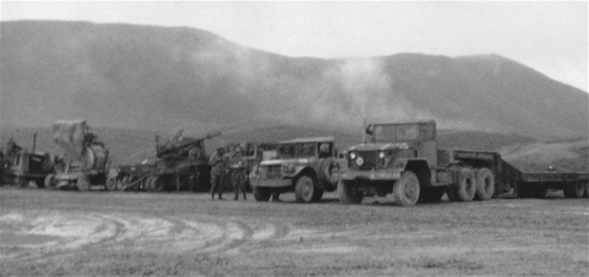 Vietnam veteran, Sp4 David Flinn, 591st Engineers, left us with this photographic record of his unit's activities in the A Shau Valley. While not professional shots, they provide a unique look into the daily activities of combat engineers. Here, Dave photographed this staging area that shows, right to left, an M123 10-ton tractor attached to M15A1 40-ton trailer, M37 3/4-ton truck, unidentified apparatus on wheels, batch concrete mixer on wheels, and unidentified.