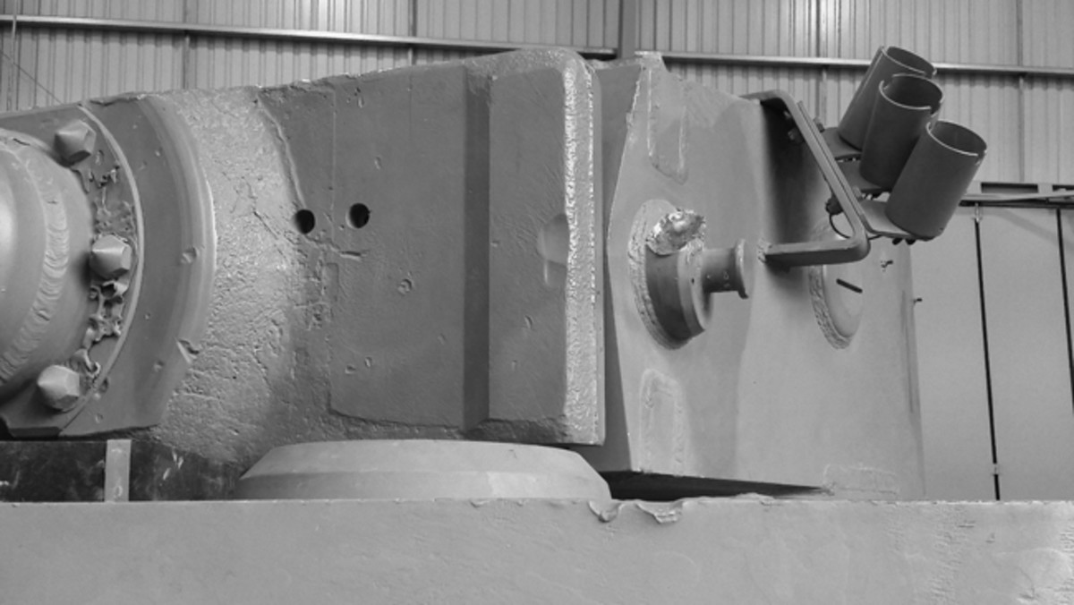 Damage is still visible to Tiger 131's cannon, mantlet, and turret was caused by a 48th RTR Churchill's six-pounder shell and is still visible. Additional damage from the engagement with 48th RTR Churchills is evident on the lifting eye, as well as on turret and rear chassis sheet metal fittings. We were able to detect what looked like machine gun shell hits on the side armor. The hull roof buckling, and other internal damage jamming the turret was repaired just after capture. No one has been able to confirm why the crew bailed out without destroying the tank per standing orders.