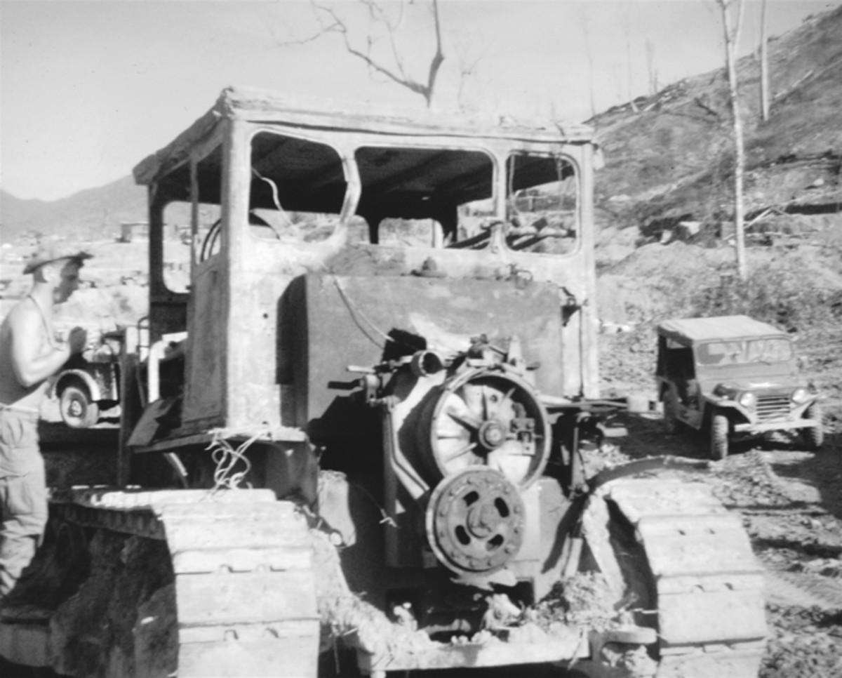 Well-worn Caterpillar D7 undergoing maintenance near Firebase Blaze in 1968. Note M151 jeep alongside.