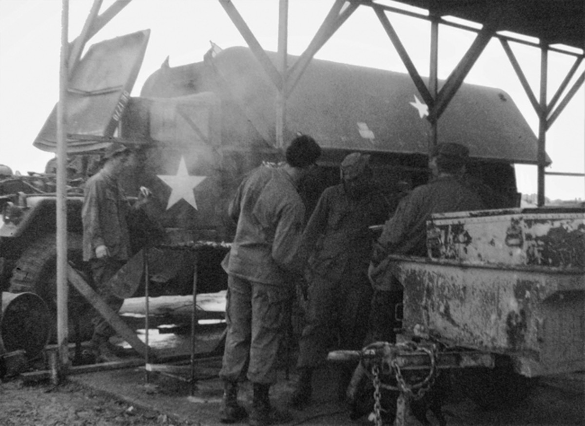 6x6 machine shop truck with gull wing doors alongside temporary work area with troops working on an undefined project.