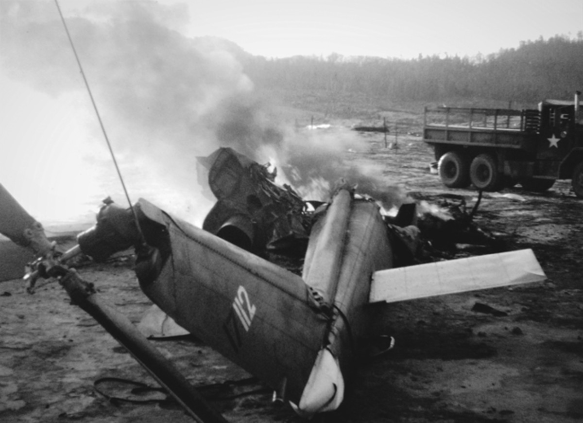 Not all helicopter crashes were shot-downs. A few minutes before the photo was snapped, this HU-1 slick was low leveling when it hit a wire. Unfortunately, not all of the crew made it out alive. Note the M35 cargo truck in background.