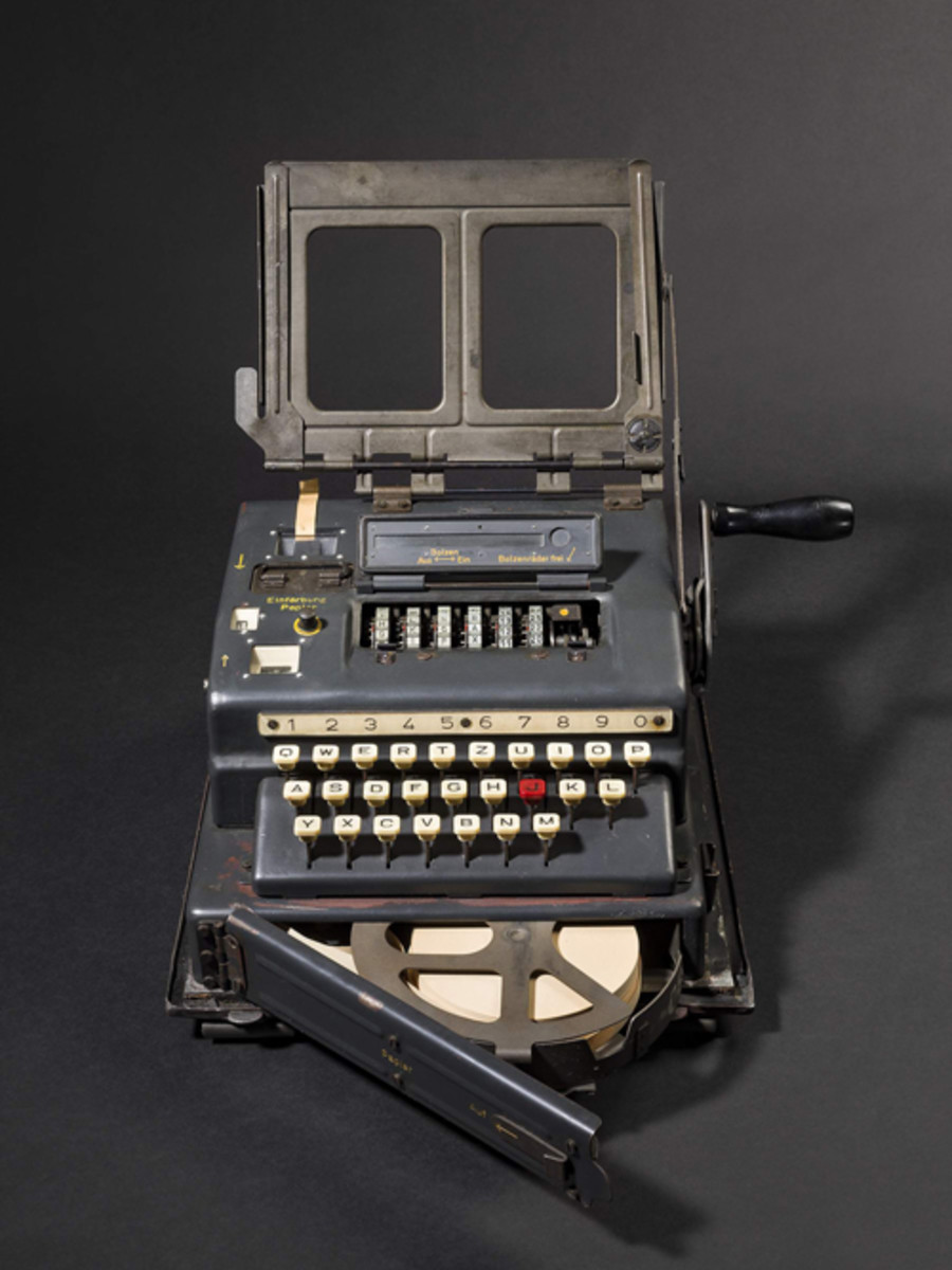 """Serial number 000352, manufacturer's code """"cxo"""" (Wanderer Werke), built in 1944. Identification plate reads """"Schl. Ger. 41 / 000352 cxo 44"""". Blue-green steel case, 26 keys, hinged document support with spring-loaded holder. Folding crank on the right hand side, hence the nickname """"Hitler Mill"""". Crank numbered """"21"""". Extractable carrying handle. Front door to insert two paper reels into a pull-out holder. Two paper reels inserted (might be postwar replacements), one to output the original, one for the encoded message. Removable inked wheel holder to colour the paper strip, its cover labelled """"1"""" and """"2"""". Two knurled wheels with 2 positions each, the left one marked """"V"""" and """"E"""", the right one marked """"F"""" and """"L"""". Left hand lever for paper transport, loose. The floor plate slightly dinged with some damage to the original paint and traces of surface rust. Sits on two wooden strips, the right one marked Eagle/HK above """"WaA69"""" (for C. Verberne Berlin/Neukölln 1936, maker of switchboards). The two small rear screws to hold the top cover, and the protective cover of the entire machine missing. Dimensions 27 x 31 x 17 cm (WxDxH), weight 10,8 kg. The device appears to be fully intact and working and is surprisingly well preserved."""