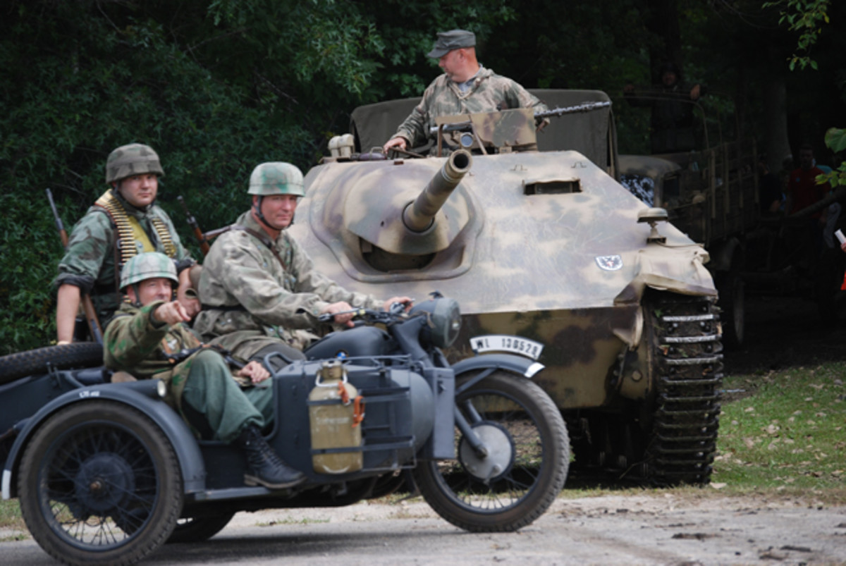 German paratroopers passing a Hetzer on the way to the front.