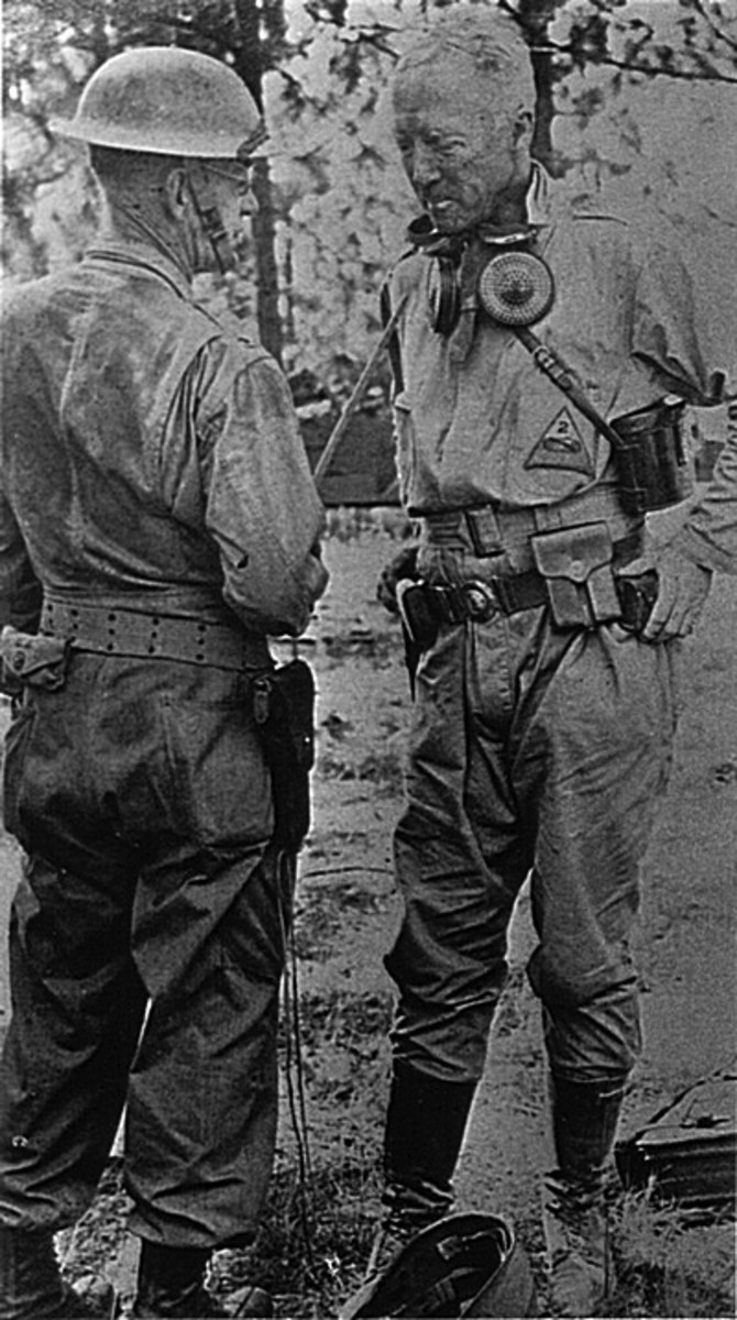 The 2nd Armor Division took part in the VII Corps Tennessee maneuvers in June 1941. Taken during those exercises, this photo shows General George Patton with an industrial-style dust respirator around his neck.