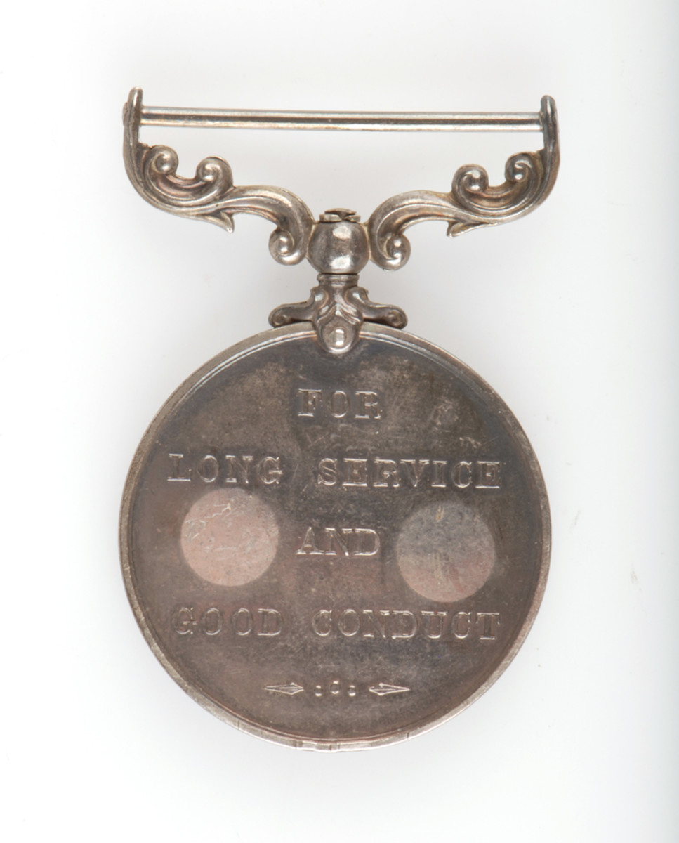 Medal planchet showing discoloration from price tags being applied to reverse.