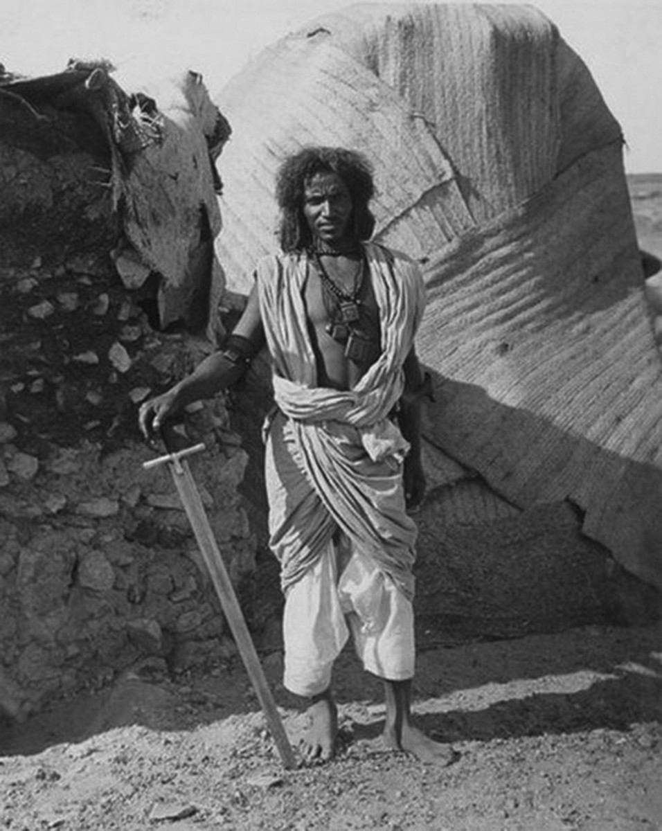 "The typical Mahdist warrior fought in sandals or barefoot. His only uniform was a plain cotton garment, known as a ""jibbah."" This warrior carries a kaskara and has a large dagger tucked in his belt. His long hair was typical of region and led to the British using the moniker ""Fuzzy Wuzzies"" to describe their foe."