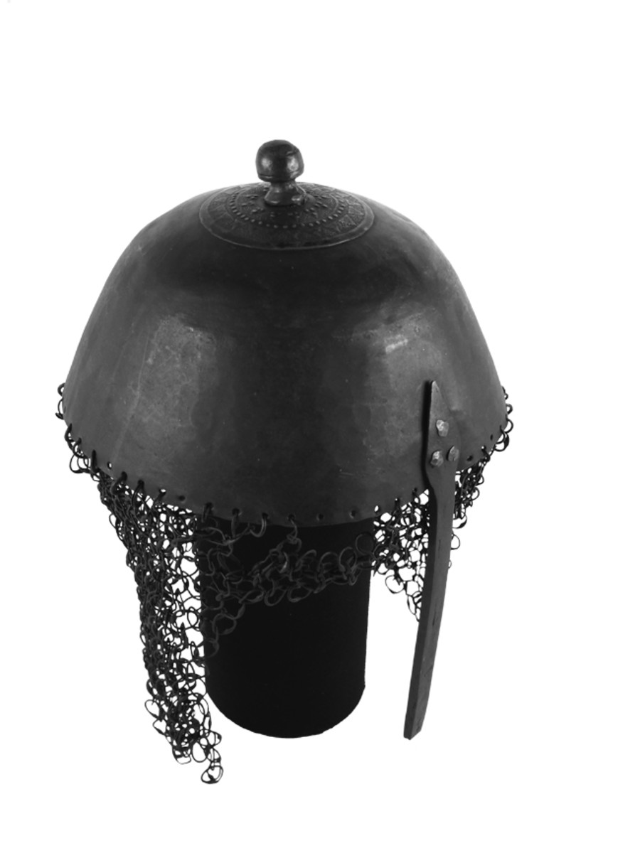 This simple helmet of Sudaneseorigin was likely based on the centuries old Indo-Persian Kula-Khud. It features a simple chain mail curtain and a fixed nose guard. Such helmets were typically only usedby the mounted Sudanese cavalry.