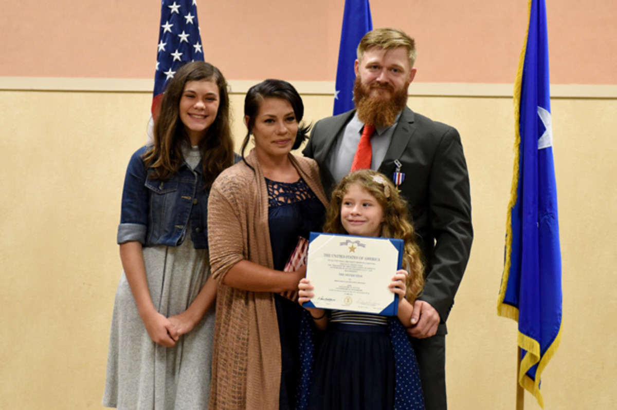 Retired Staff Sgt. Benjamin Hutchins, 18th Air Support Operations Group joint terminal attack controller, and his family pose for a photo during a ceremony where he received the Silver Star Medal, Nov. 4, 2016, at Pope Army Airfield, North Carolina. Hutchins received the Silver Star for attempting to save drowning soldiers in the face of imminent danger during a deployment in 2009 in Bala Murghab, Afghanistan. (U.S. Air Force photo by Airman Miranda A. Loera)