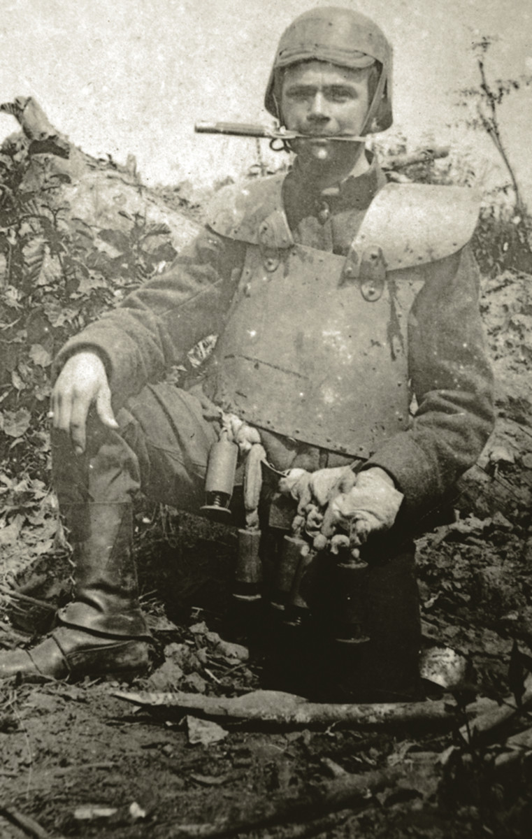 """As the Great War bogged down into a trench slug- fest, armies of both sides produced and carried a vast array of close-combat weapons including small, versatile weapons that the combatants would come to call, """"trench knives."""" This Belgian soldier wearing body armor and a Farina-style helmet, carries a modified Mauser bayonet in his teeth. John Adams-Graf collection"""