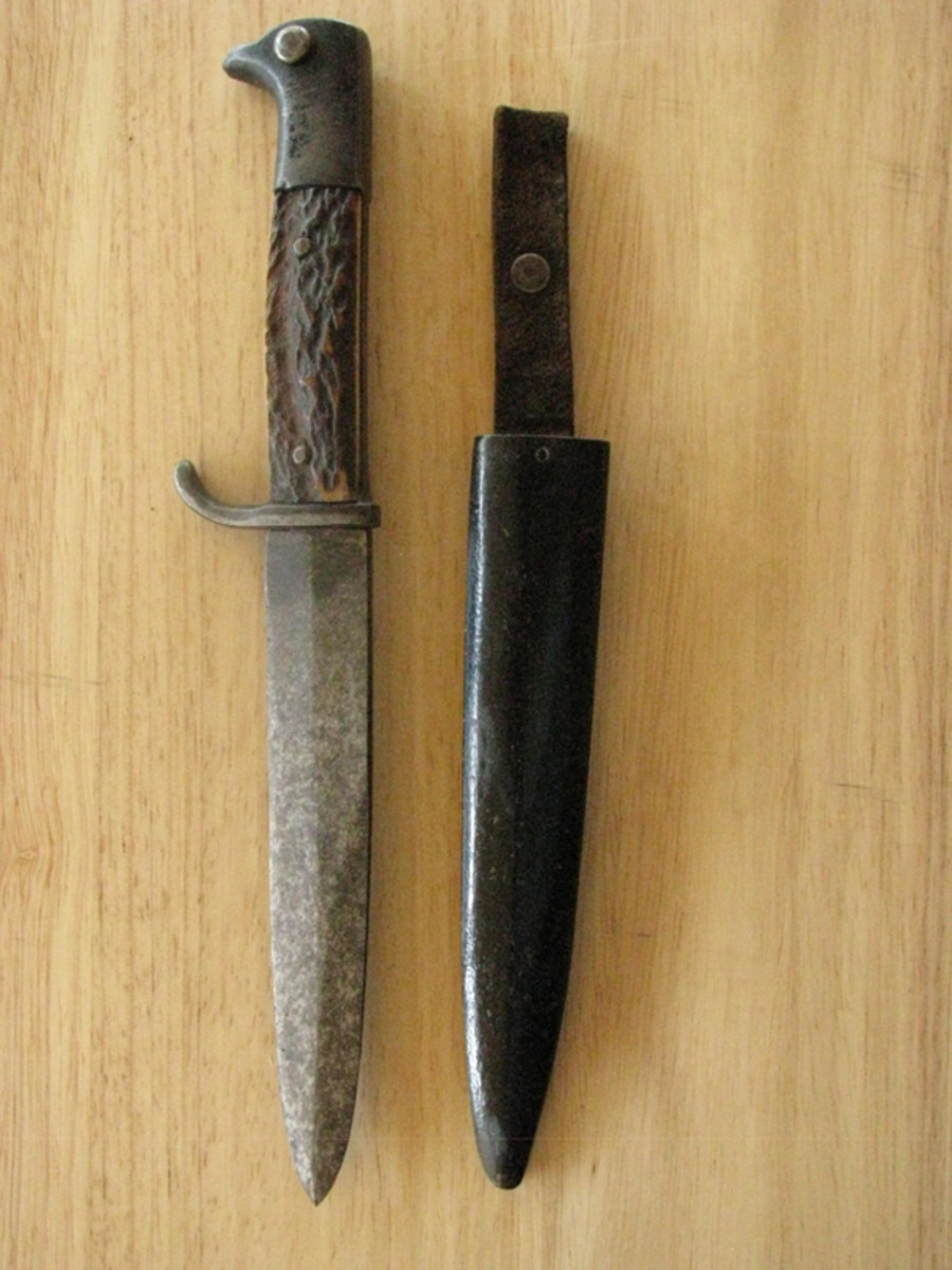 This knife saw a lot of service, but the substantial double-edged blade, stag handles, and blackened pommel with button show that it was once a high quality privately purchased piece.
