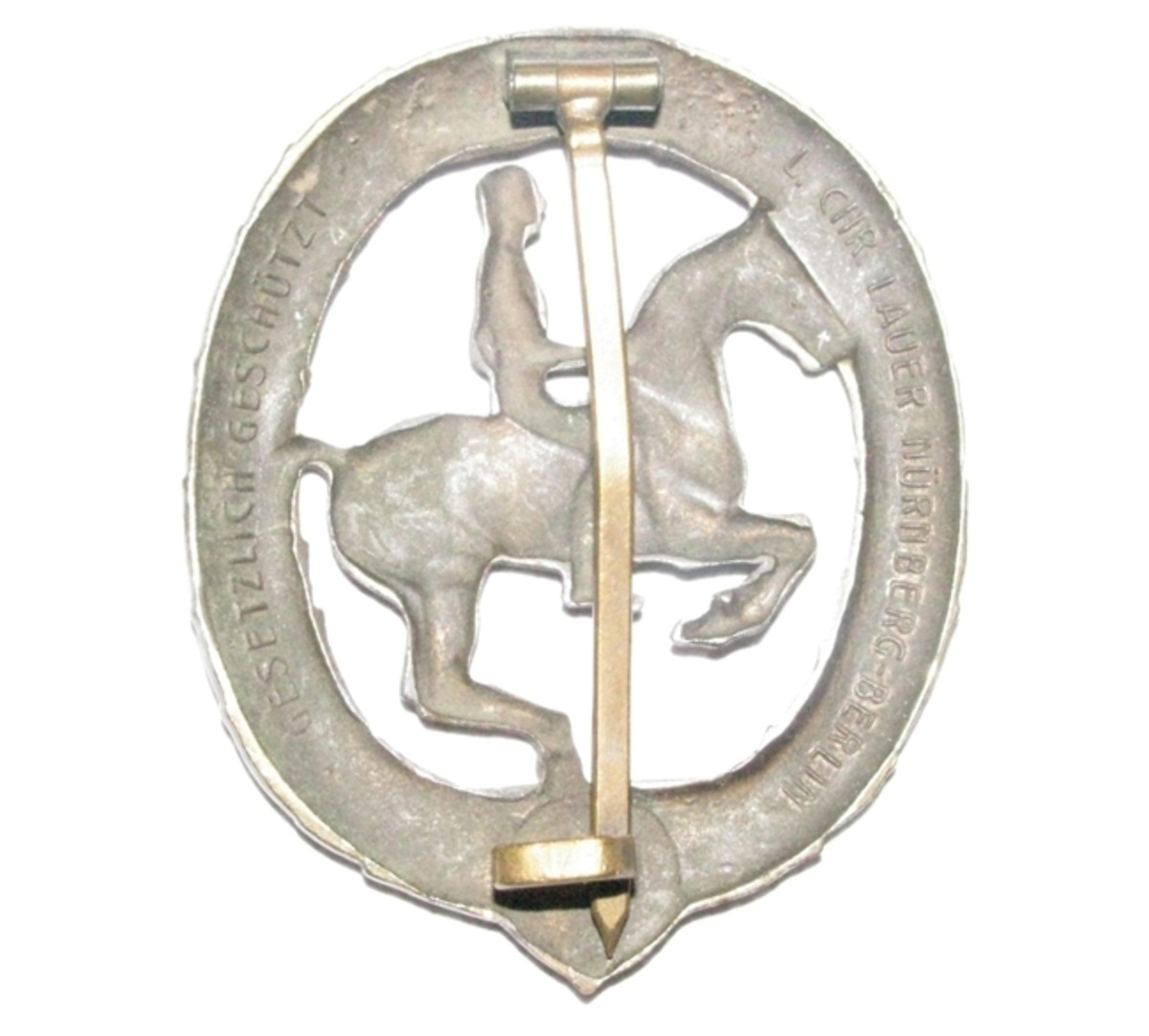 This bronze badge was manufactured by Lauer company. The reverse features a broad attachment pin and hook assembly.