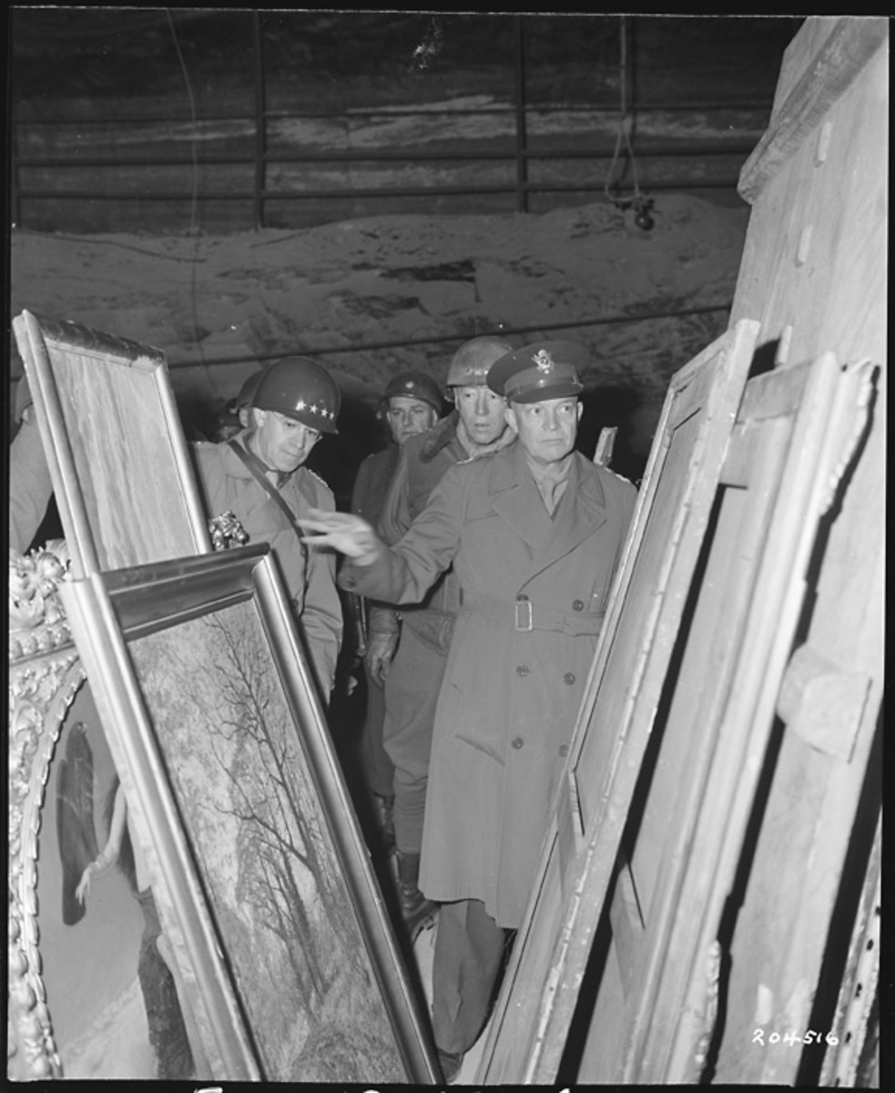 General Dwight D Eisenhower, Supreme Allied commander, inspects art treasures looted by the Germans and stored away in the Merkers salt mine. Behind GEN Eisenhower are General Omar N. Bradley (left), CG of the 12th Army Group, and (right) LT Gen George S. Patton, Jr, CG, 3rd U.S. Army. 4/12/45. (RG 111-SC-204516)